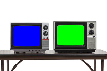 Two vintage televisions isolated on table with chroma key blue and green screens.
