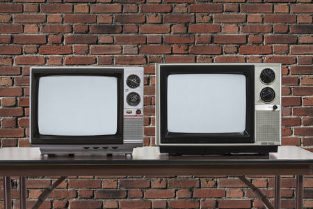 Two vintage televisions on table with brick wall.