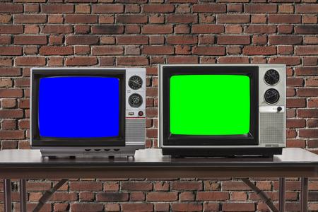 Two vintage televisions with brick wall and chroma key blue and green screens. 版權商用圖片