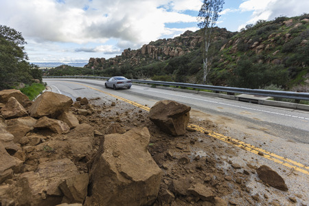 Los Angeles, California, USA - February 18, 2017:  Car passes storm caused rockslide on Santa Susana Pass Road in the San Fernando Valley.