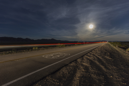 Route 66 sign with full moon and streaking train in the California Mojave desert.