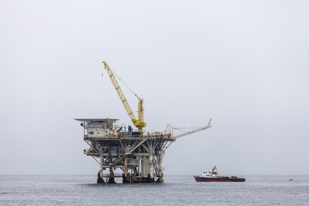Ventura County, California, USA - June 4, 2017:  Active oil and gas rig with ship in the Santa Barbara Channel near the Southern California Coast. Editorial
