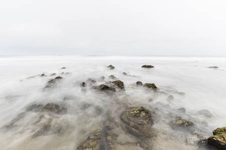 Foggy pacific ocean tidal pool with motion blur at Point Dume in Malibu California.