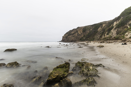 Dume Cove with motion blur waves and clouds in Malibu, California