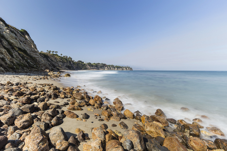 Rocky shore with motion blur waves at secluded Dume Cove in Malibu, California. Stock Photo