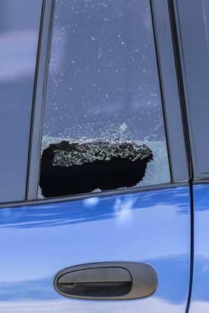Smashed car door window from vehicle burglary.