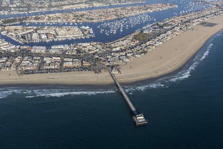 Aerial view of Newport Beach pier, homes, beach and harbor in Orange County, California.