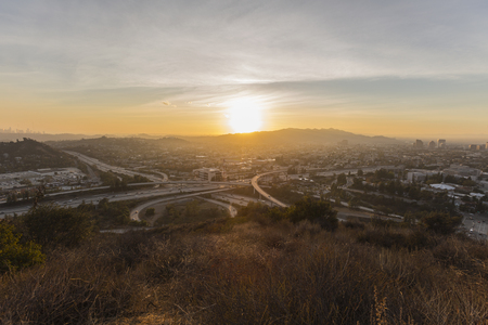 View of sun setting behind Griffith Park, Glendale and the Santa Monica Mountains in Los Angeles, California.