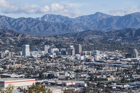 Downtown Glendale with the San Gabriel Mountains in background.  View from hilltop at Griffith Park in Los Angeles California. Stock Photo