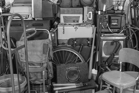 Vintage garage storage area with old tools, gardening, music and sports equipment in black and white. Stock Photo