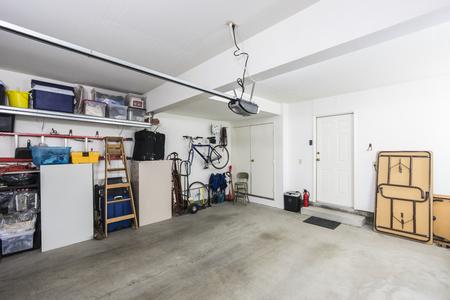 Garaje residencial suburbano organizado limpio para dos automóviles con herramientas, archivadores y equipo deportivo.
