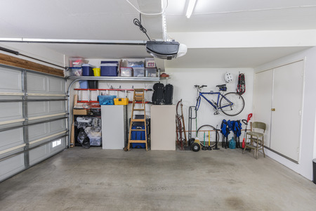 Organized clean suburban residential two car garage with tools, file cabinets and sports equipment.