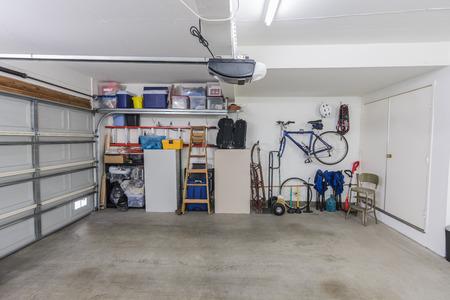 Garaje para dos autos residencial suburbano limpio organizado con herramientas, archivadores y equipo deportivo.