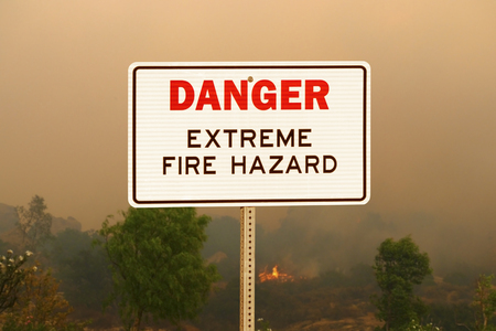 Danger extreme fire hazard sign with wildfire background.