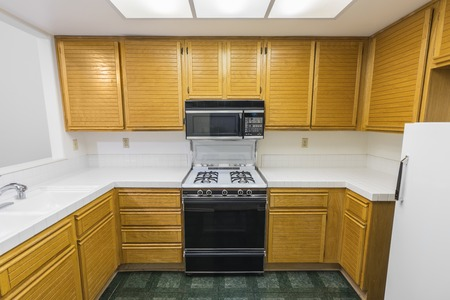 Old condo kitchen with oak cabinets, tile countertops, gas stove and green vinyl flooring.  Unchanged since 1988. Reklamní fotografie