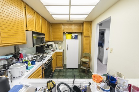 Messy condo kitchen with oak cabinets, tile countertops, gas stove, green flooring and piles of dishes. 免版税图像