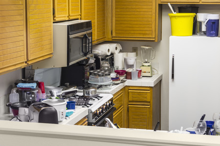 Messy old kitchen with oak cabinets, tile countertops, gas stove, green flooring and piles of dishes.