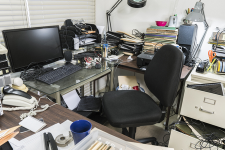 Messy business office desk with piles of files and disorganized clutter. Banque d'images