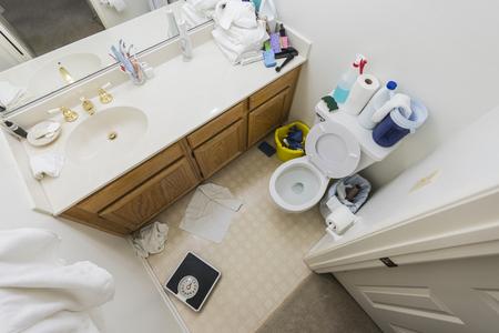 Piccolo bagno disordinato con asciugamani sporchi e disordine per la pulizia.