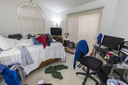 Camera da letto disordinata e disordinata di ragazzi adolescenti con pile di vestiti, musica e attrezzature sportive.