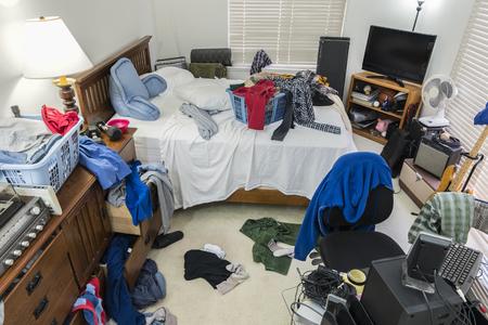 Bardzo brudna, zagracona sypialnia nastolatka ze stosami ubrań, muzyki i sprzętu sportowego.
