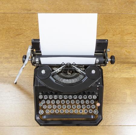 Vintage black typewriter on old oak table.