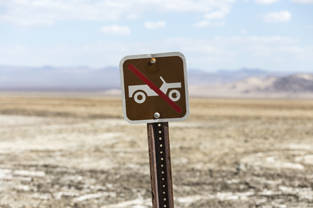 Old no off road driving sign with Mojave desert dry lake in background.  Shot near Zzyzx in Southern California.
