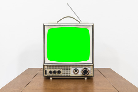 Grungy vintage portable television on table with chroma green screen.
