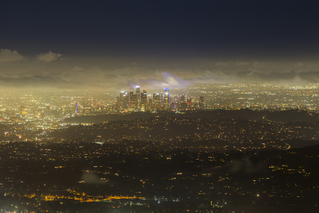 Foggy night aerial cityscape skyline view of urban downtown Los Angeles buildings in Southern California.   스톡 콘텐츠