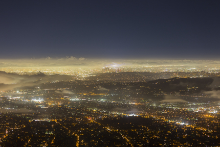 Night fog aerial view of urban downtown Los Angeles skyline in Southern California.