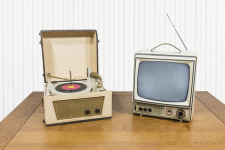 Vintage portable record player and television on old wood table. 免版税图像