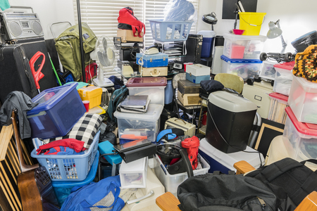 Hoarder room packed with stored boxes, electronics, files, business equipment and household items. Stock Photo