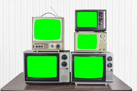 Cinq téléviseurs vintage sur une vieille table en bois avec des écrans verts chroma key