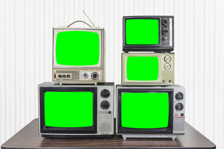 Five vintage televisions on old wood table with chroma key green screens