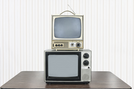 Two vintage television stacked on old table.