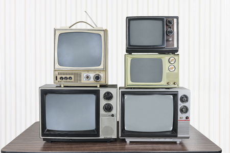 Five vintage televisions stacked on old wood table.