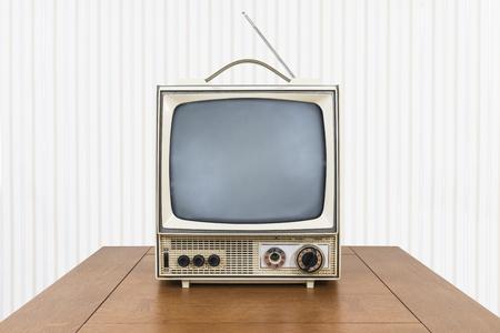 Televisión portátil vintage sucio en la mesa de madera vieja. Foto de archivo