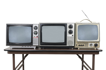 Three vintage televisions on wood table isolated on white with clipping path.
