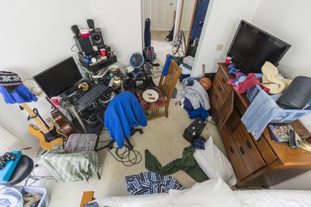 Bardzo zabałaganiona, zagracona sypialnia nastoletnich chłopców na przedmieściach ze stosami ubrań, muzyki i sprzętu sportowego.