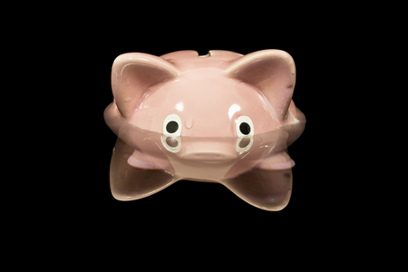 Vintage piggy bank toy up to its eyeballs in deep dark water. Stock Photo