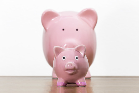 Large and small pink piggy banks representing parent with child.