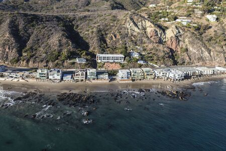Aerial view of Malibu shoreline homes and Santa Monica Mountains slopes north of Los Angeles on Highway 1 in Southern California.