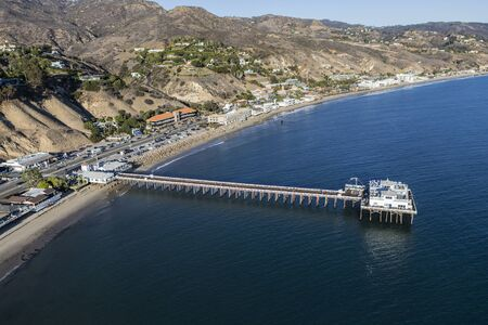 Aerial of historic Malibu Pier, Pacific Coast Highway and Santa Monica Bay near Los Angeles in scenic Southern California.