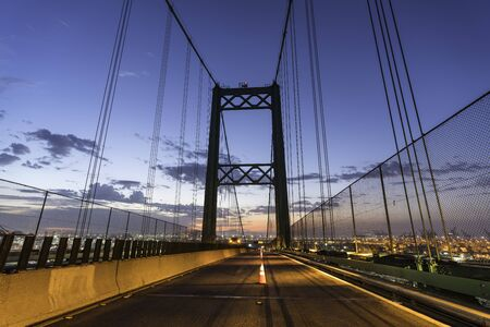 Early morning cones dividing lanes on the Vincent Thomas Bridge in Los Angeles, California. Imagens