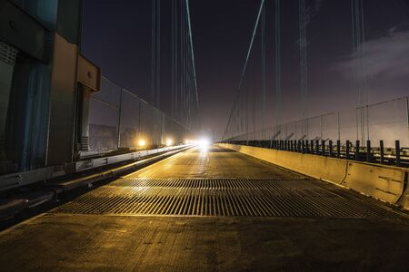 Night view of Vincent Thomas Bridge road grates and on coming headlights in Los Angeles, California. Фото со стока