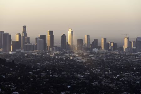 Downtown Los Angeles buildings reflecting early morning sunlight through the haze.