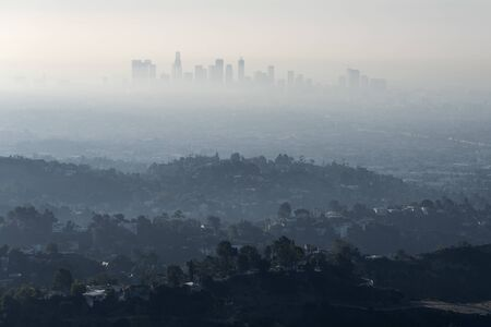 Thick hazy layer of smog and smoke from nearby brush fire clouding the view of downtown Los Angeles buildings in Southern California.   Shot from hilltop in popular Griffith Park. Stock fotó