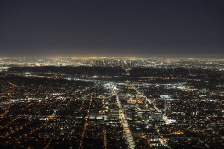 Night mountaintop view of downtown Glendale with Los Angeles California towers in background.
