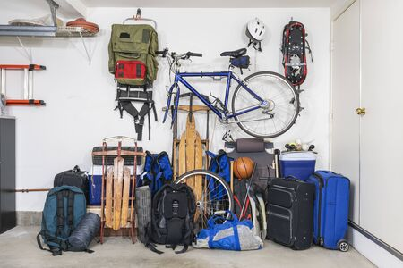 Sports and travel gear and equipment in piles in corner of messy suburban garage. Stock fotó