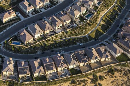 Aerial late afternoon view of suburban residential rooftops in the San Fernando Valley area of Los Angeles, California.